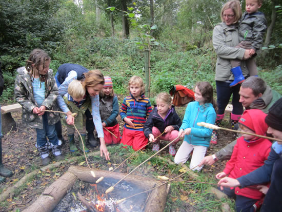children toasting damper bread over a fire