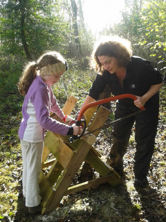 woman using bow saw with young girl
