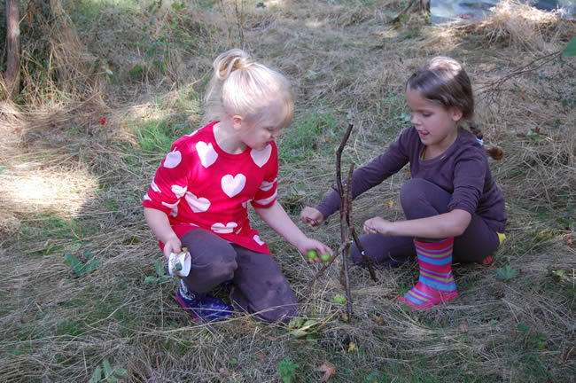 two girls creating a pixie house from twigs