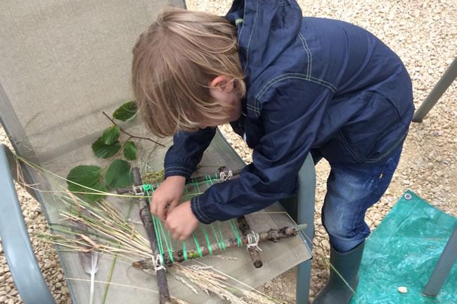 boy working on twig loom