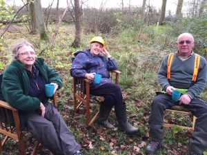 three people sitting in woodland drinking tea