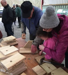 man, woman and child looking at bird box pieces on table